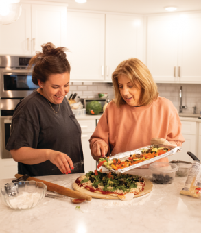 two woman cooking in a kitchen