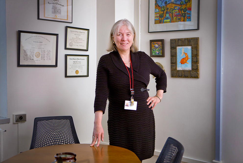 a woman standing posing for a photo in her office.
