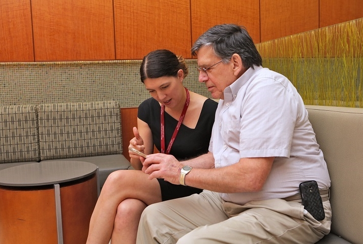 Dr. Heather Yeo (left) demonstrates the mHeals app for patient David Matthews, who participated in her pilot study. Photo credit: John Abbott