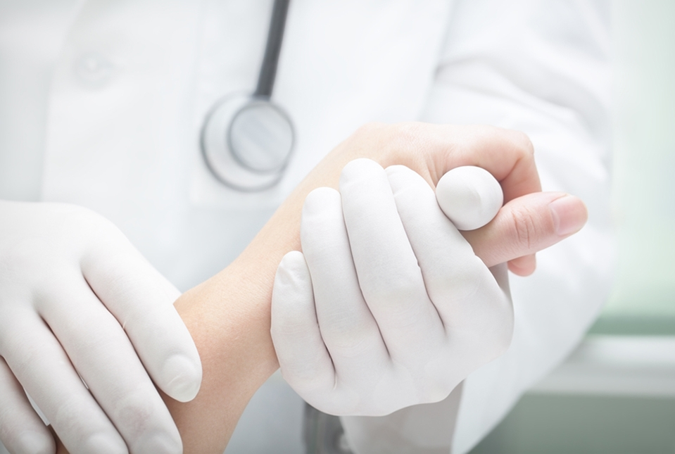 gloved doctor holding patient hand