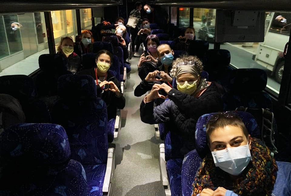 People posing together in a bus wearing protective face masks