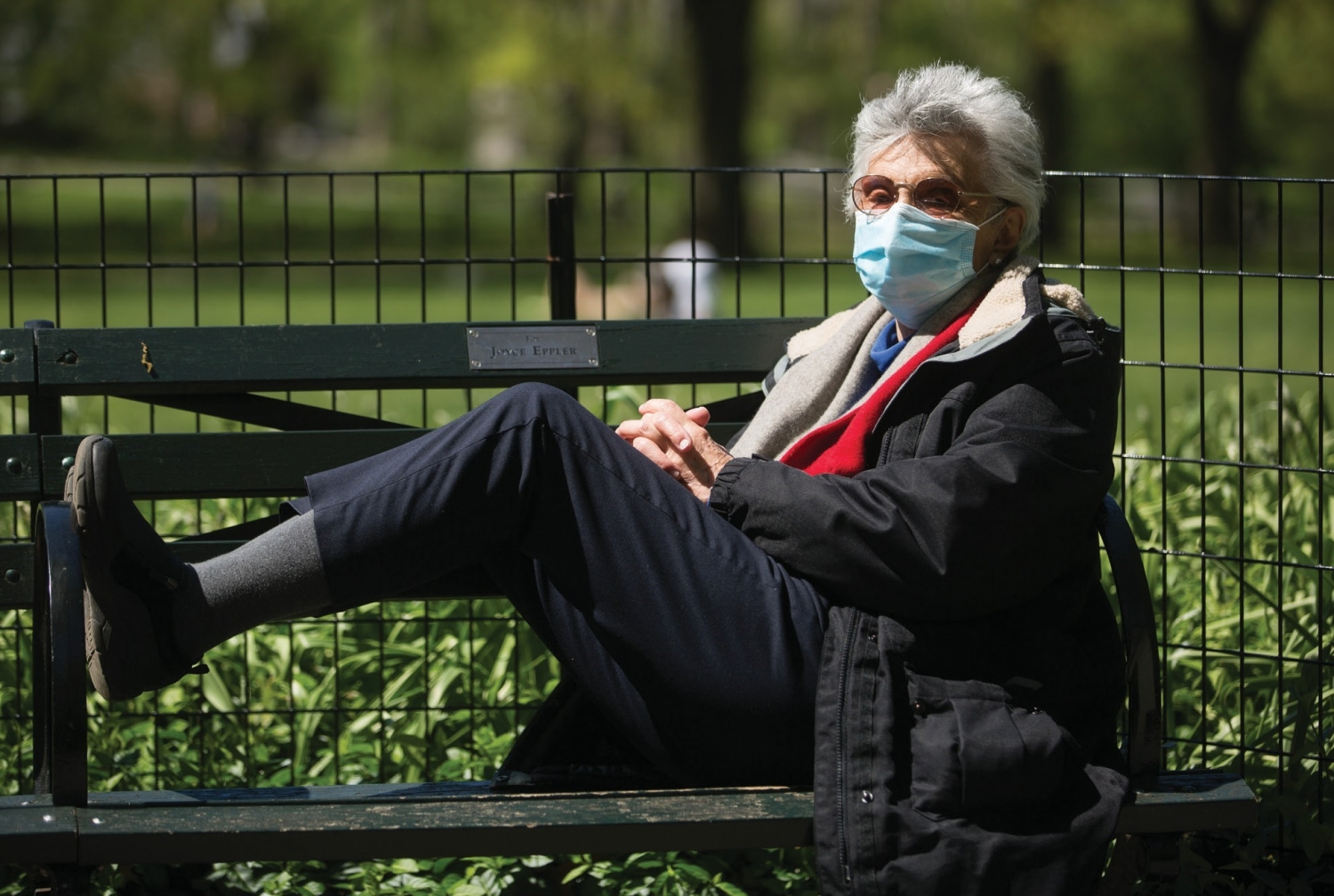 a woman on a bench wearing a face mask