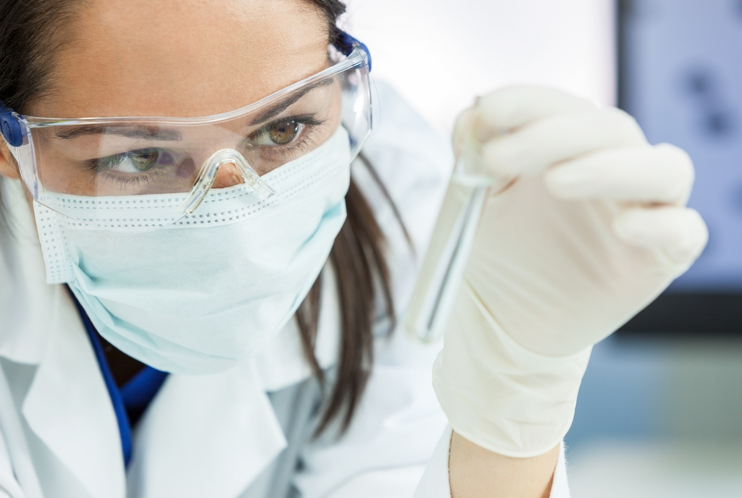 a woman wearing a protective face mask holding a test tube in a lab