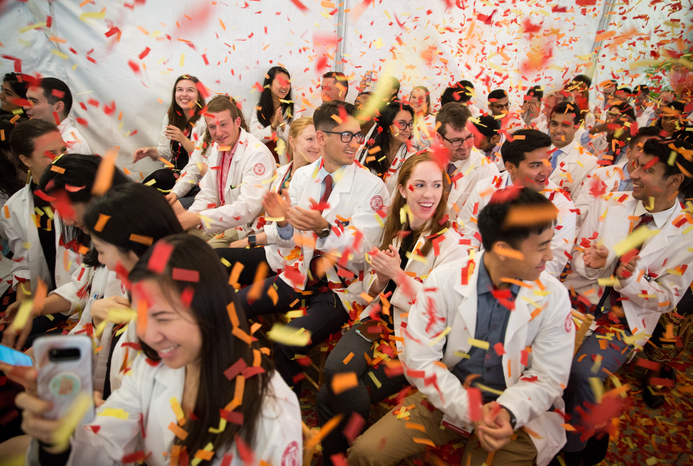 students at an event celebrating the while confetti flies around the room