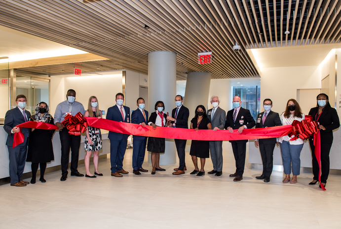 A group of people holding a red ribbon during a ribbon-cutting event.