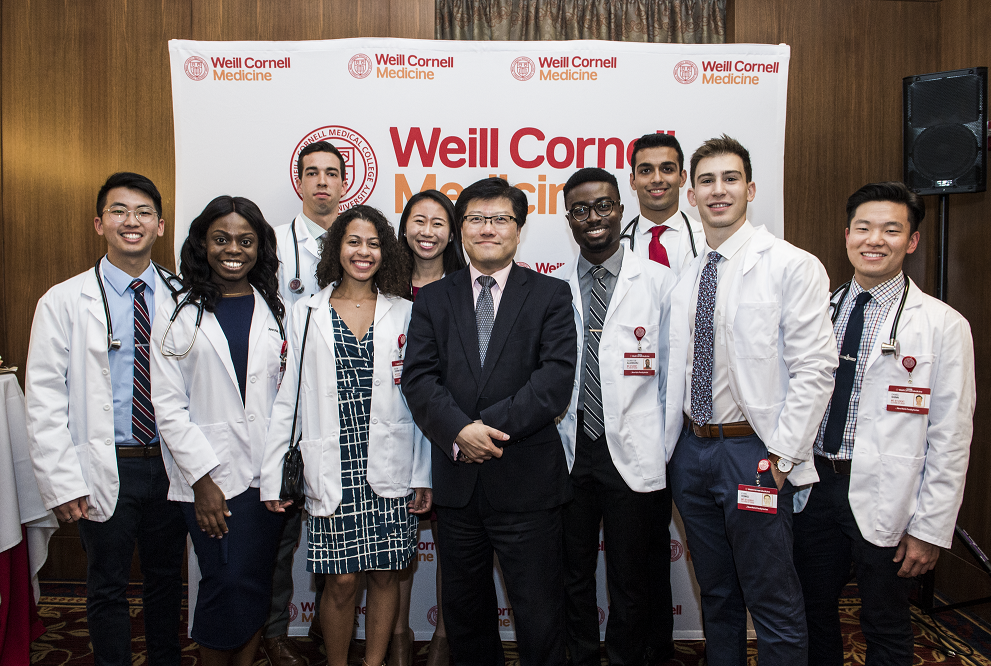 First-year medical students celebrate receiving their white coats with Dean Augustine M.K. Choi.