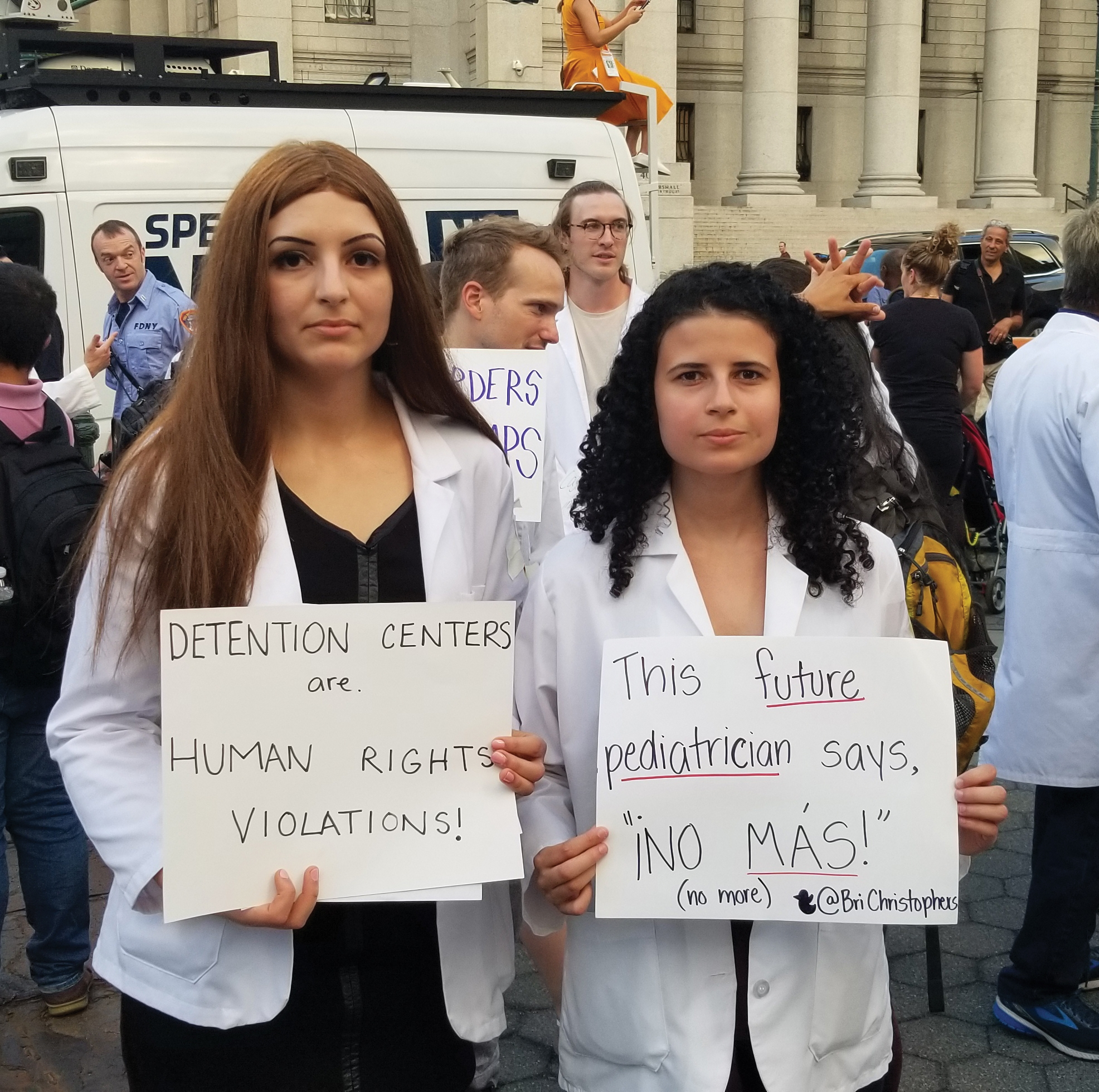 two woman holding up signs in protest