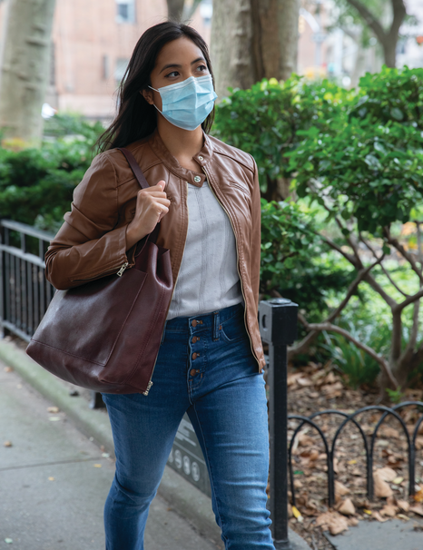 a woman walking with her mask on
