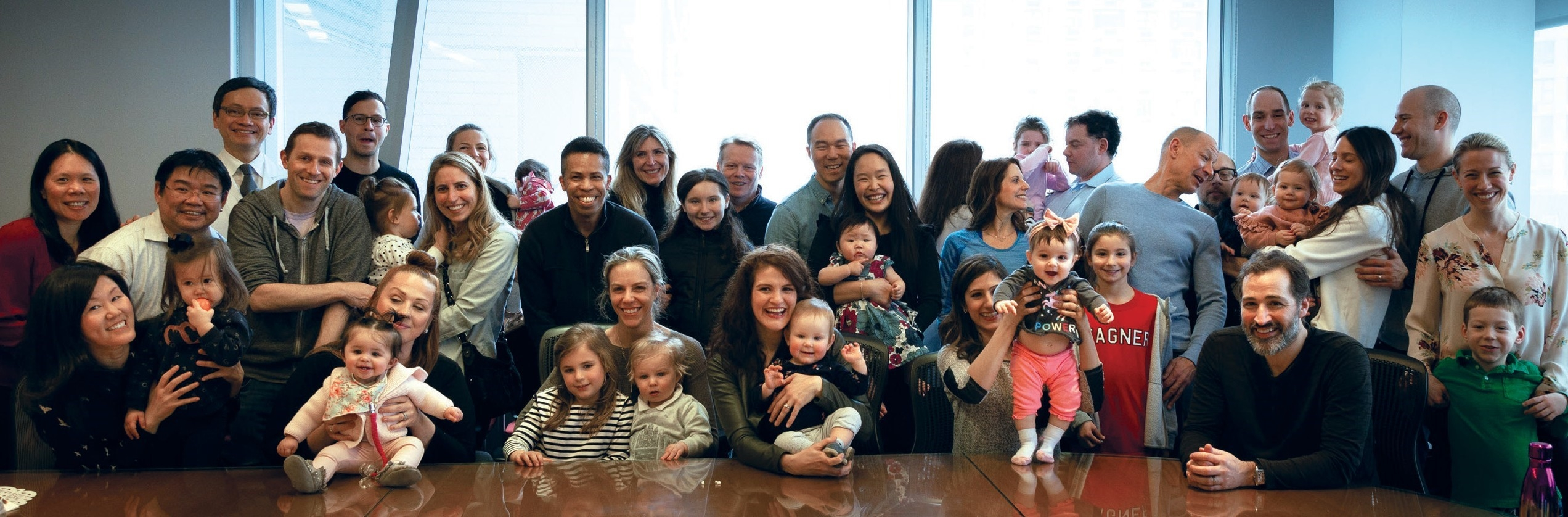 a large group with babies posing for a photo.