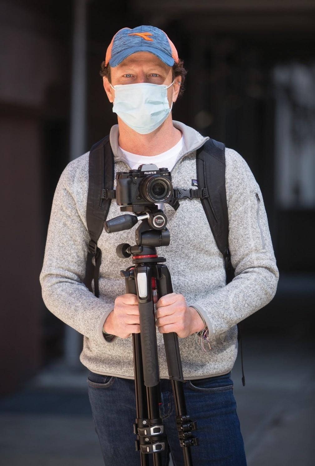 A man wearing a face mask holding a tripod