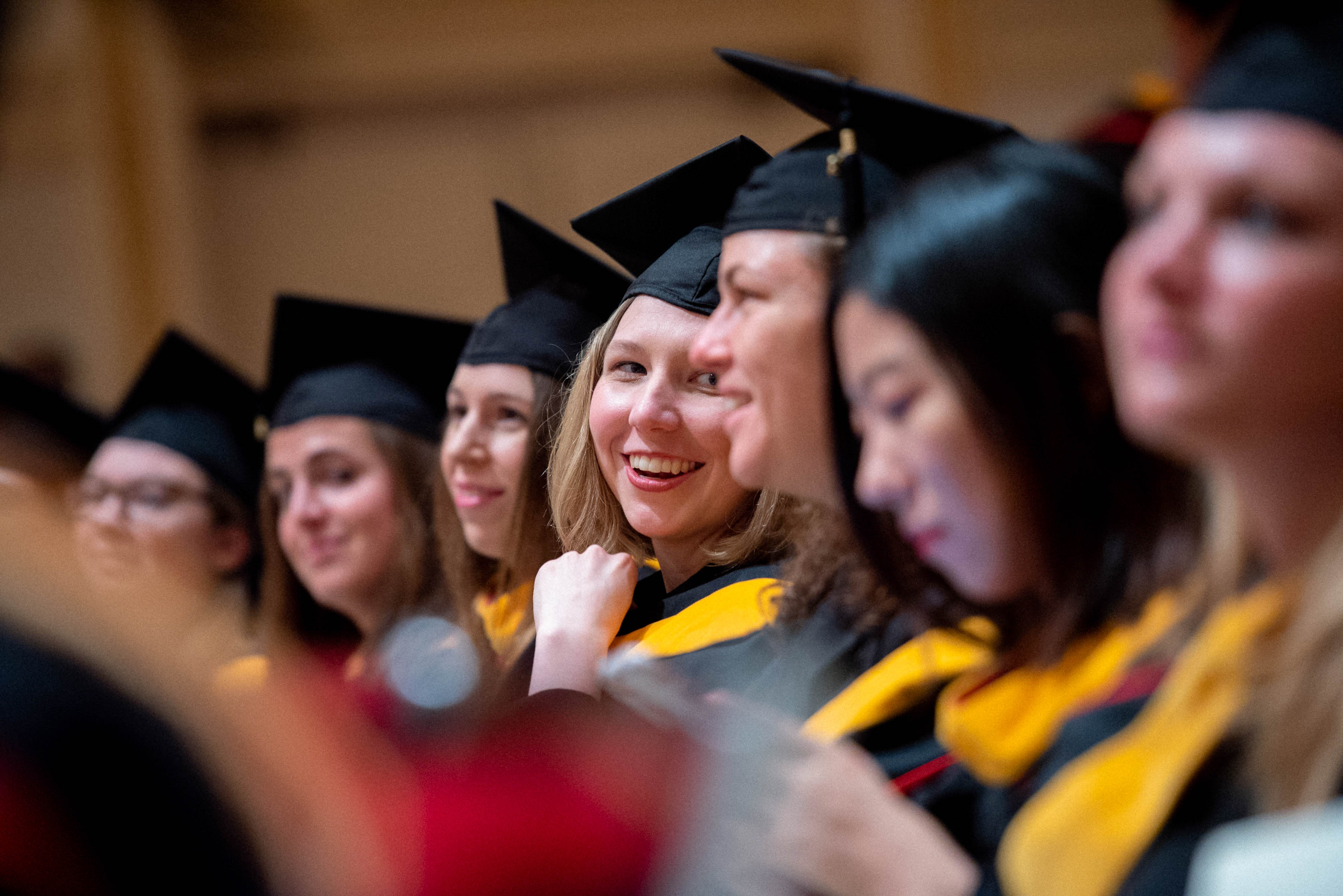 Graduates earning Master of Science degrees share a smile during commencement.
