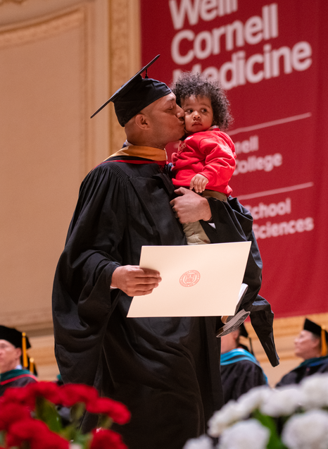 Edwin Zambrano-Acosta crosses the stage with his daughter to receive his master's degree in healthcare policy and research.All photos taken by Amelia Panico. Click photo to view the full Commencement Flickr gallery.