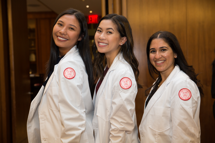 Three girls pose for a picture at the PA white coat ceremony