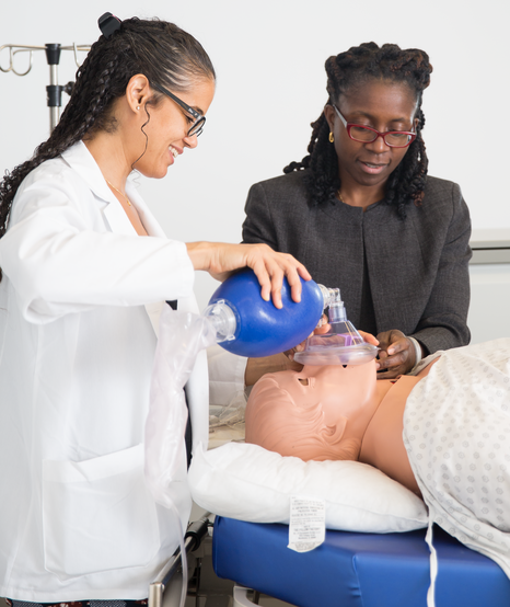Using a dummy that simulates a patient's responses, Francesca Voza '20 (left) practices bagging in the Margaret and Ian Smith Clinical Skills Center with guidance from Dr. Joy Howell, associate professor of clinical pediatrics and vice chair for