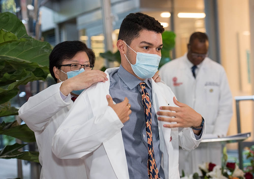 Dr. Augustine Choi coats a student