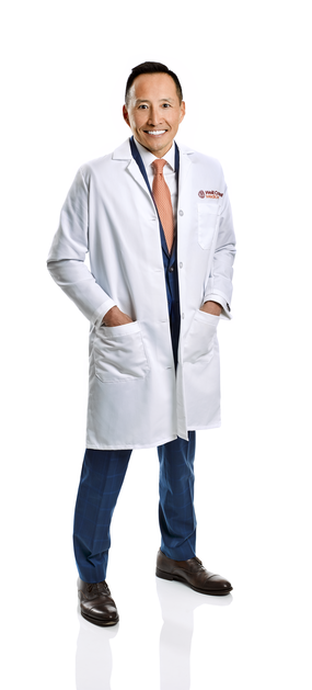 a man in a white coat posing and smiling