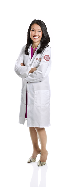 a woman in a white coat smiling