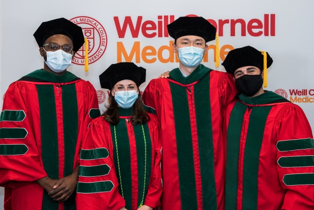 Masked graduating students standing in front of a WCM backdrop