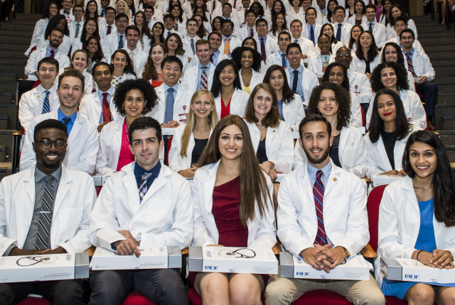 Students from the class of 2022 sit in Uris Auditorium with their White Coats, smiling at the camera.